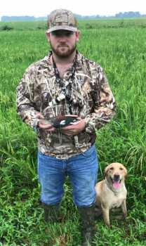 Phillip Zaunbrecher, 23, of Mowata, poses with his dog Bella and the South American ringed teal he shot over rice stubble near Eunice on Sept. 21.